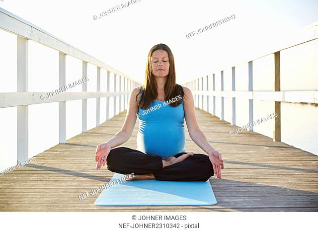 Pregnant woman practicing yoga at seaside