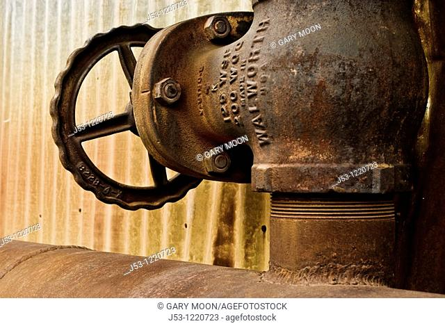 Old rusty pipe valve on abandoned steam plant