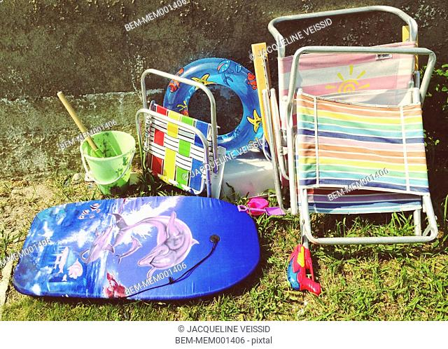 Lawn chairs, boogie board and sand bucket in backyard