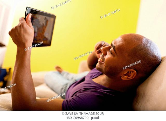 Mid adult male on sofa holding digital tablet and mobile phone