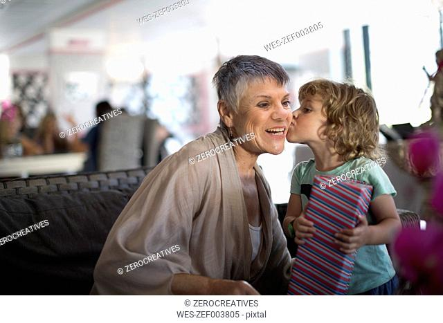 Grandmother getting a kiss from grandchild who received a gift