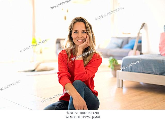 Portrait of smiling woman sitting on the floor at home