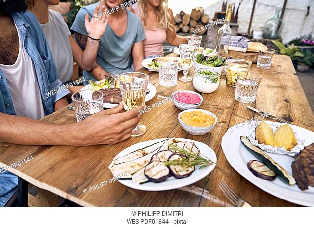 Friends having fun at a barbecue party, eating together