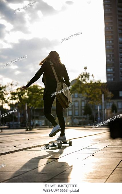 Rear view of young woman riding longboard in the city