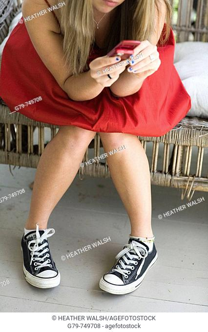 Teenage girl texting on her cell phone