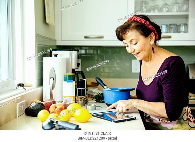 Caucasian woman using digital tablet in kitchen
