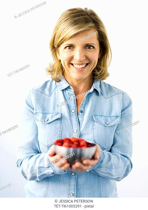 Portrait of Mature woman holding bowl with raspberries