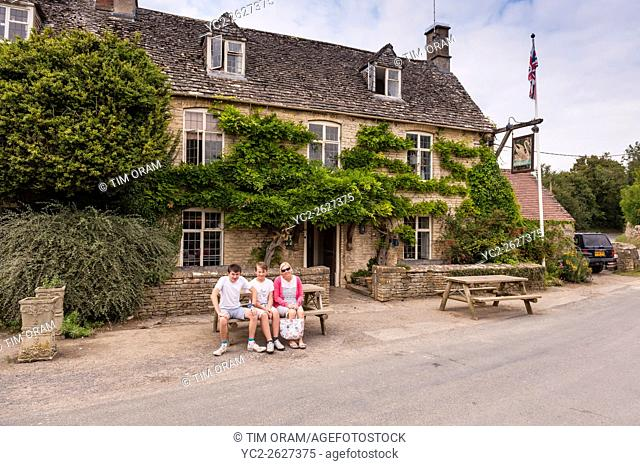 A family outside the Swan Inn at Swinbrook near Burford , Oxfordshire , England , Britain , Uk