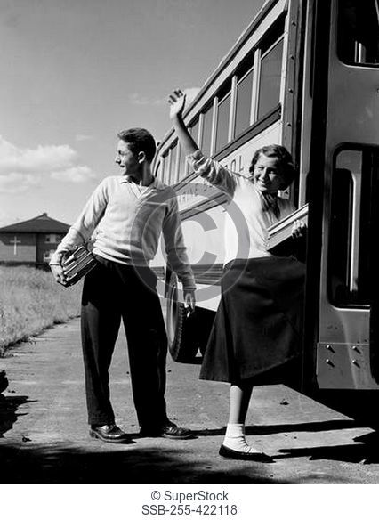 Teenage girl and boy boarding school bus