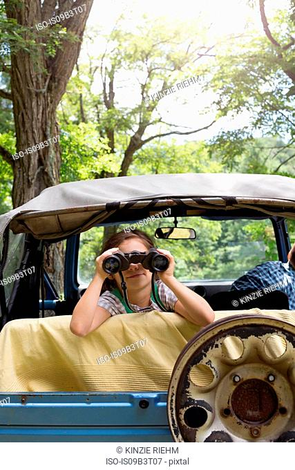 Young girl looking out of off road vehicle, using binoculars
