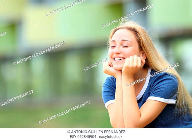 Happy teenage student relaxing meditating outdoors sititng in a campus