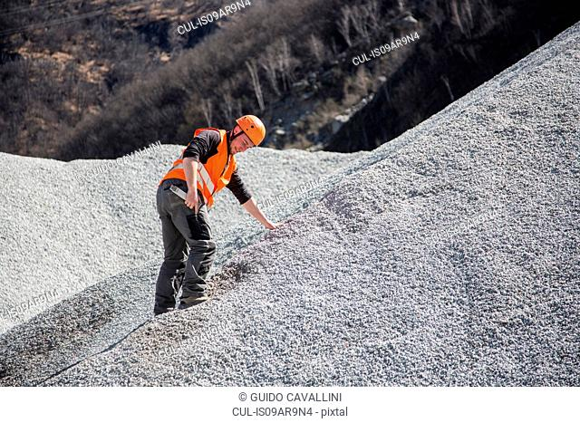 Quarry worker measuring on gravel mound at quarry