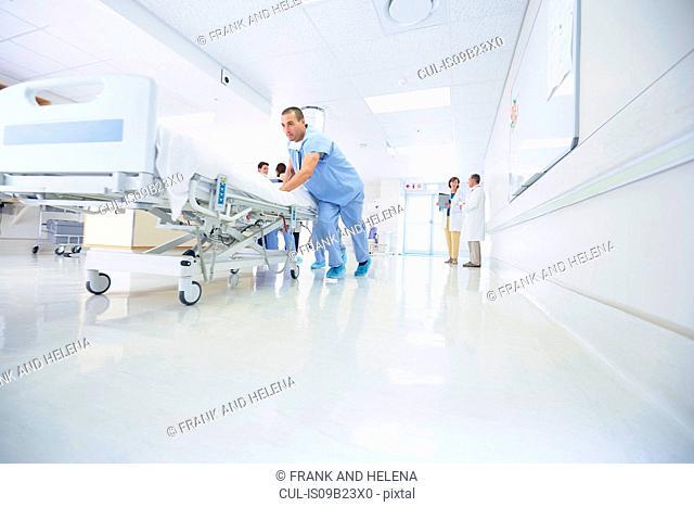 Medics urgently pushing hospital bed along corridor