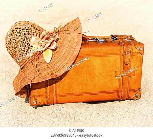Suitcase and straw hat on rest on a seashore