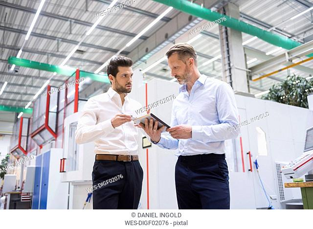 Two businessmen with tablet in factory shop floor discussing