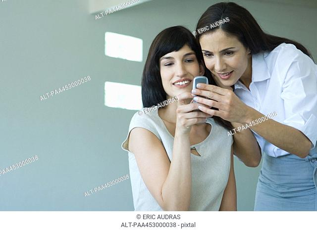 Two businesswomen looking at cell phone, smiling, cheek to cheek, waist up