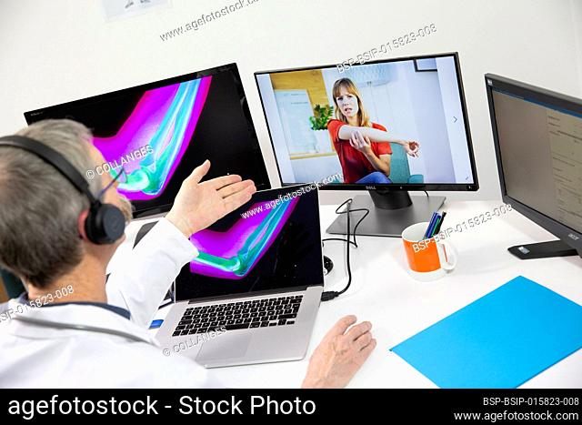 A young woman having a video consultation with a male GP for elbow pain and an elbow x-ray