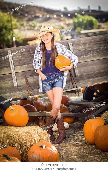 Preteen Girl Wearing Cowboy Hat Portrait at the Pumpkin Patch in a Rustic Setting