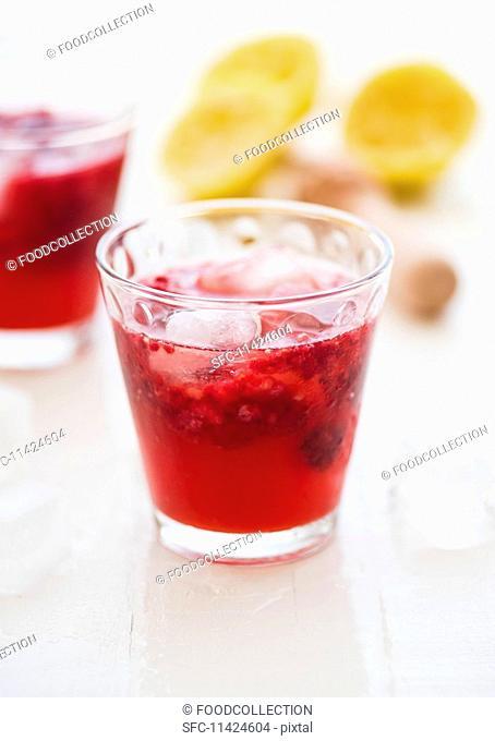 Raspberry lemonade with lemon juice and ice cubes