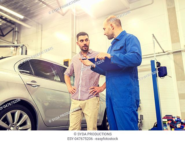 auto mechanic with clipboard and man at car shop