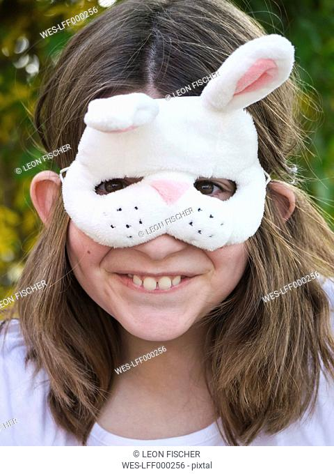 Germany, Bavaria, Close up of girl wearing easter bunny mask, smiling, portrait