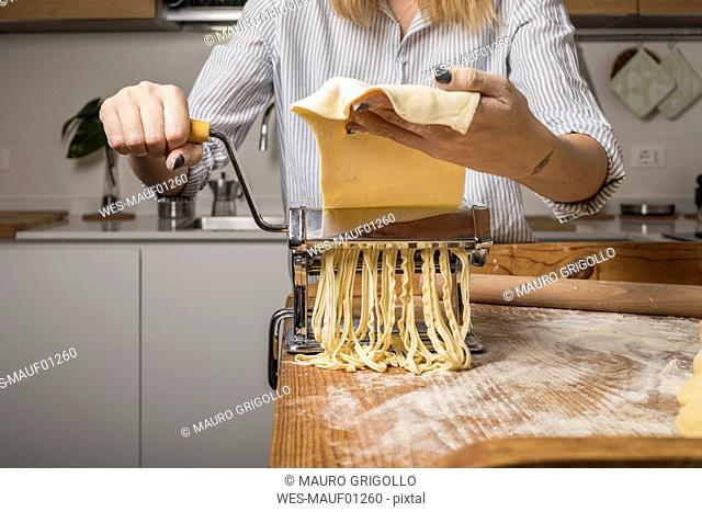 Woman preparing homemade pasta, using pasta maker