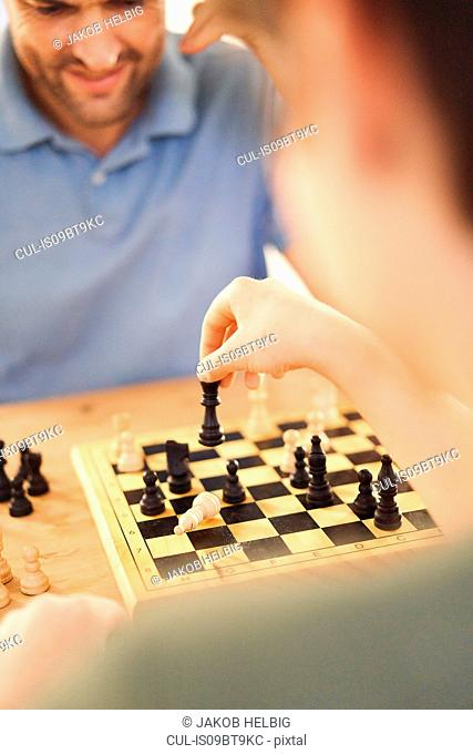 Boy and father playing game of chess at living room table,over shoulder close up