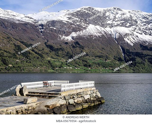 bench on pier at Dalsören campsite, viewpoint, snow covered mountains at the fjord, Lustrafjord, inner branch of the Sognefjord, Norway
