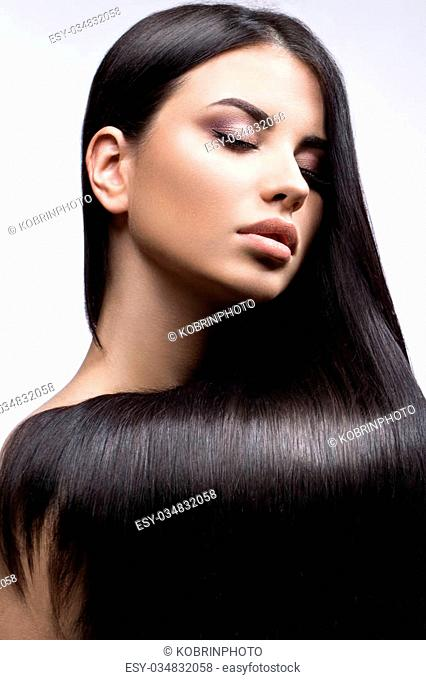 Beautiful brunette girl in move with a perfectly smooth hair, and classic make-up. Beauty face. Picture taken in the studio on a white background