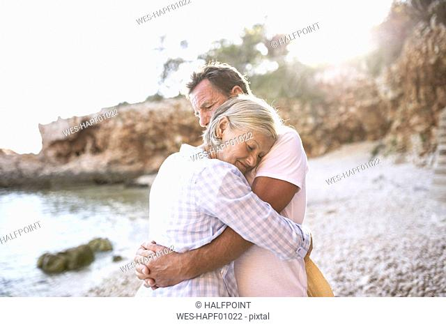 Happy senior couple hugging on the beach