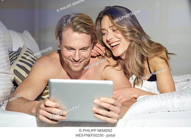 Portrait of relaxed couple with tablet lying on bed