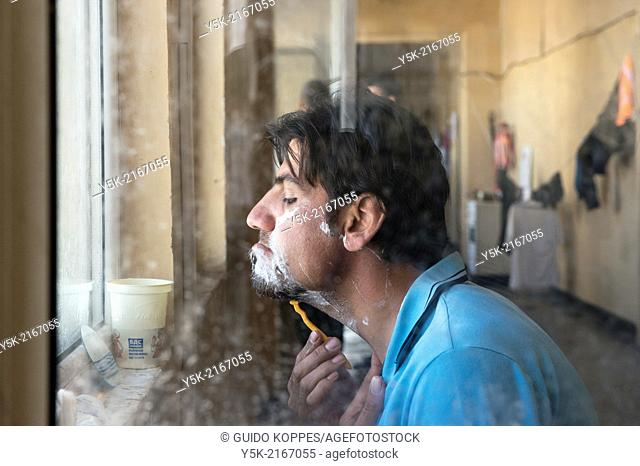 Sofia, Bulgaria. Male, Syrian refugee in refugee camp Voenna Rampa shaving in front of an open window
