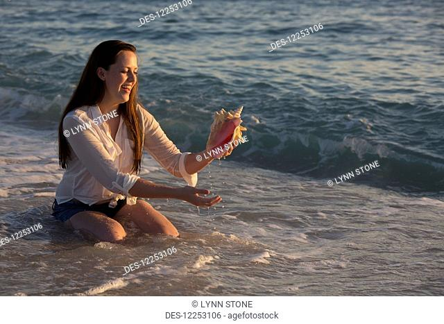A young woman finds a seashell in the ocean at sunset; Nokomis, Florida, United States of America
