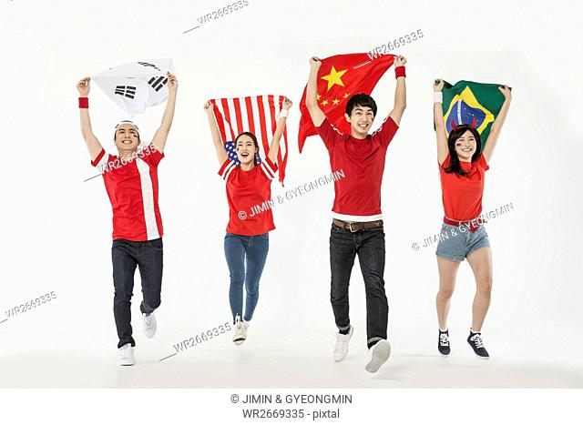 Young smiling cheerleaders running holding national flags