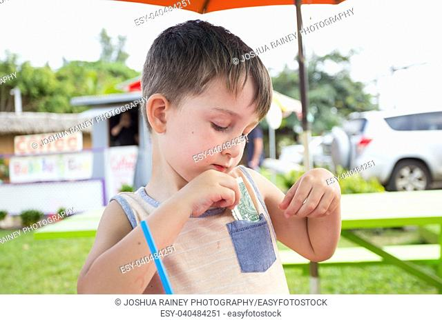 Five year old boy putting money into his pocket while on vactation in Oahu Hawaii traveling