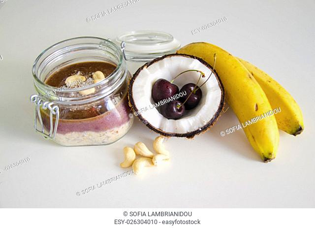 Cherry coconut banana overnight oats with cracked open coco, banana, cashews mixed with chia seeds and cherry cream in a mason jar
