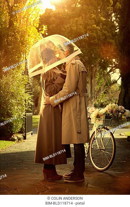 Caucasian couple hugging under umbrella