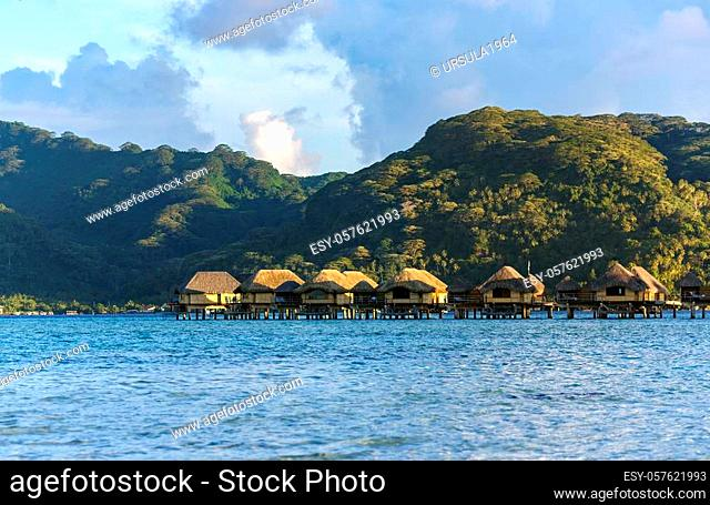 Luxury overwater thatched roof bungalow resort on a wooden pontoon in the rays of sunset on Bora Bora in French Polynesia