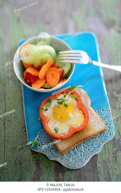 A fried egg flower on toast served with vegetable salad