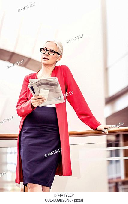 Businesswoman reading newspaper on office balcony