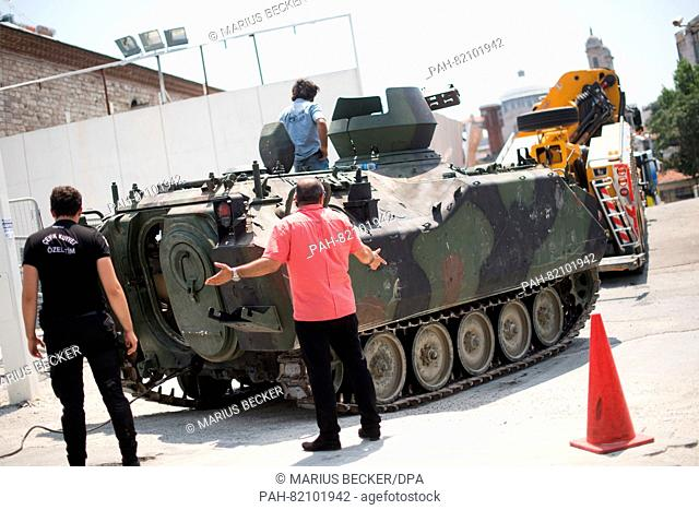 Police officers and workers remove a tank at Taksim Square in Istanbul, Turkey, 17 July 2016. Turkish authorities said they had regained control of the country...