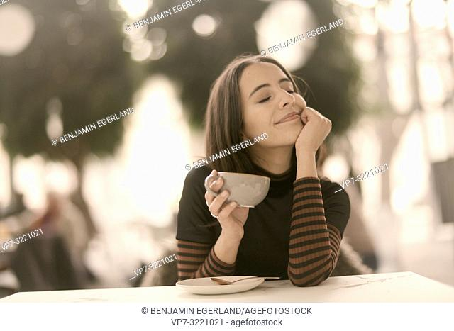portrait of pleased woman holding coffee cup while enjoying break at table in café, closed eyes, pure happiness, joy, in Munich, Germany