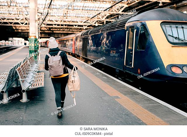 Woman walking to train at platform, Edinburgh, Scotland