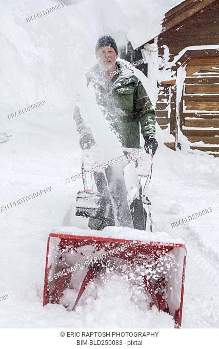 Caucasian man pushing snow blower