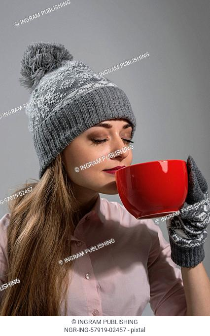 Woman in winter clothes enjoying a hot drink eyes closed on gray background