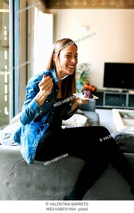 Happy young woman eating a healthy dessert at home
