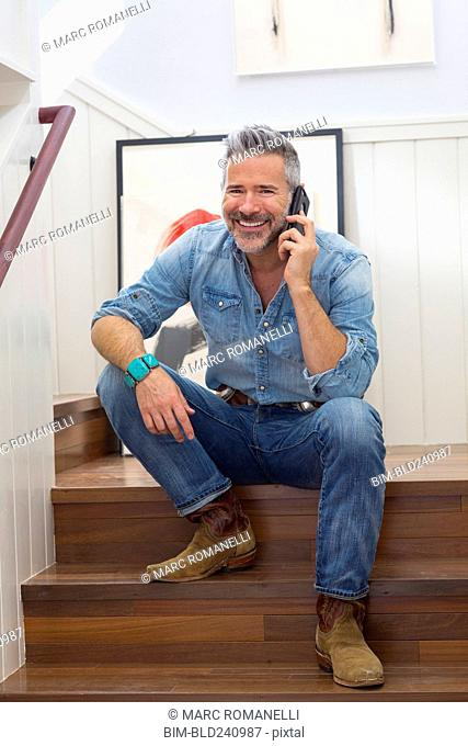 Caucasian man sitting on staircase talking on cell phone