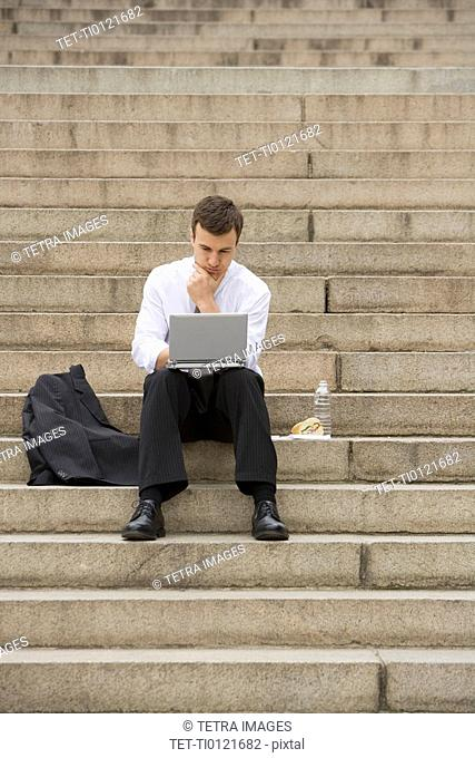 Man sitting outdoors on stairs with laptop