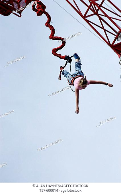 Woman bungee jumping from crane