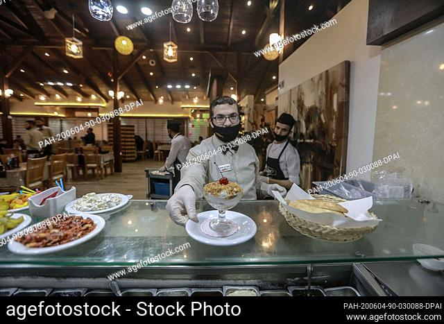 04 June 2020, Palestinian Territories, Gaza City: A waiter wearing a face mask serves at a restaurant in Gaza City, following the easing of the Coronavirus...